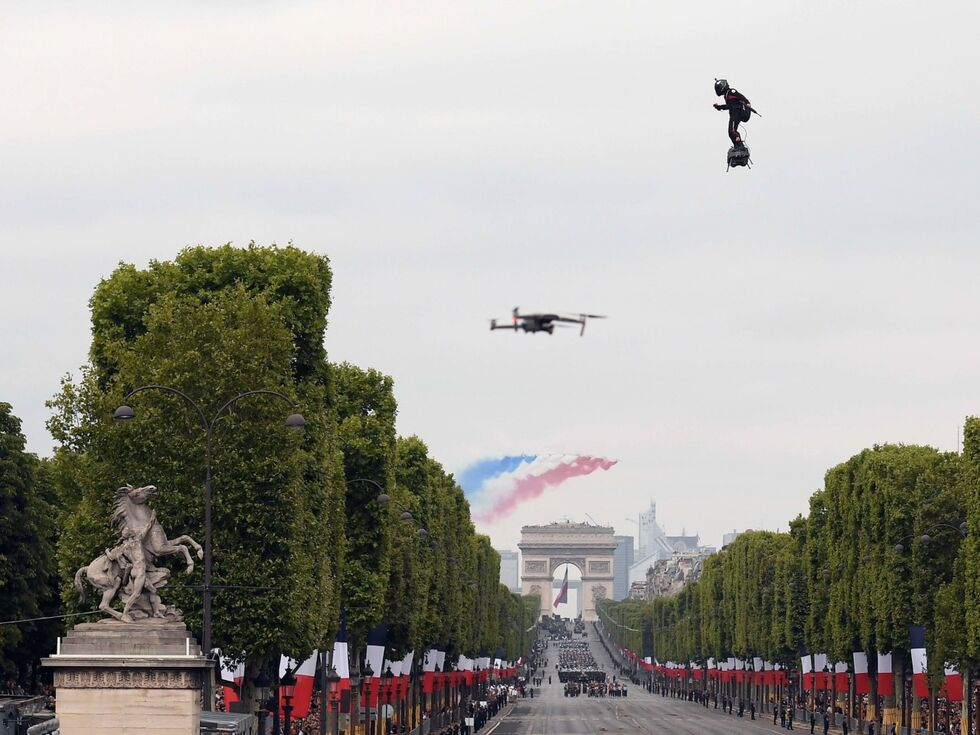 """14. Juli 2019 – Bei der traditionellen Militärparade in Paris war heuer ein """"fliegender Mann"""" die Hauptattraktion. Der französische Jetski-Rennfahrer Franky Zapata flog auf einem sogenannten Flyboard Air über die Champs-Elysees. Er hatte ein Gewehr in der linken Hand. Das Flyboard weckt schon seit längerem das Interesse des Militärs:"""